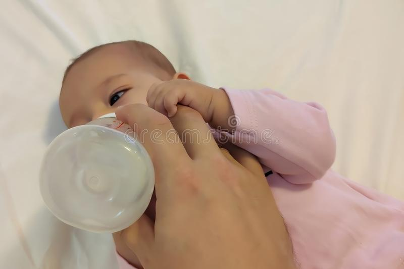 Dziecięcy dziewczynki łasowania mleko od butelki obrazy royalty free