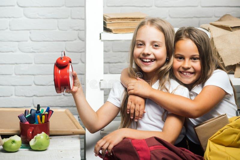 Dzieciństwa i szczęścia pojęcie szczęśliwy dzieciństwo szczęśliwe małe dziewczynki z zegarem przy szkolną sala lekcyjną obrazy stock