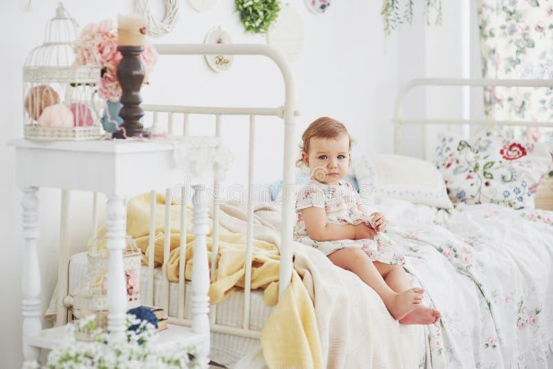 Dzieciństwa pojęcie dziewczynka jest usytuowanym przy łóżkiem bawić się z zabawkami domem w ślicznej sukni Biały rocznika childro obraz stock