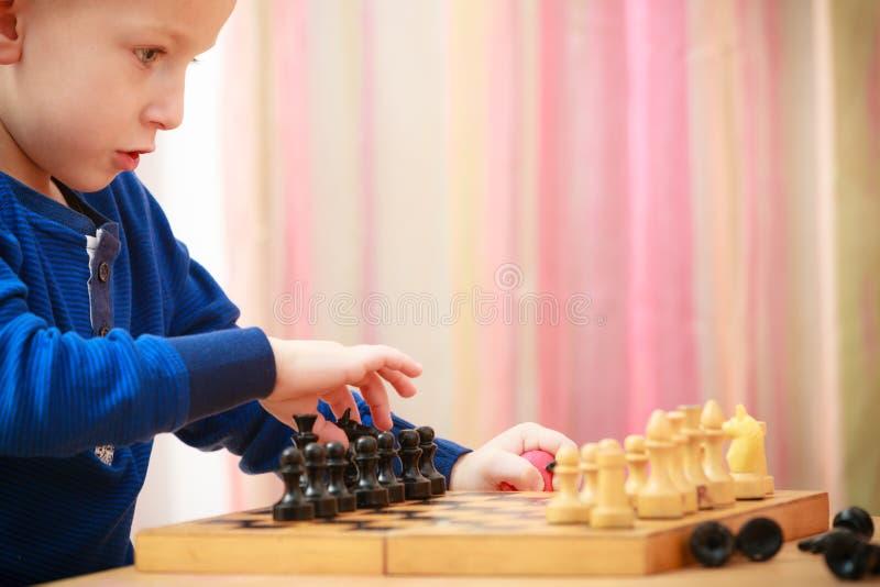 Dzieciństwo. Inteligentny chłopiec dziecka dzieciak bawić się szachy. W domu. obraz stock