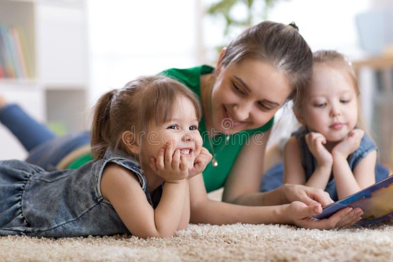 Dzieci śmia się zabaw czytelnicze opowieści z ich matką kłaść na podłoga w domu i ma obrazy stock