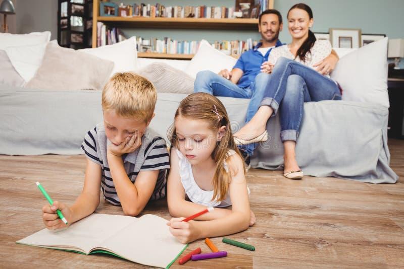 Dzieci barwi na książce podczas gdy rodzice patrzeje one zdjęcia royalty free