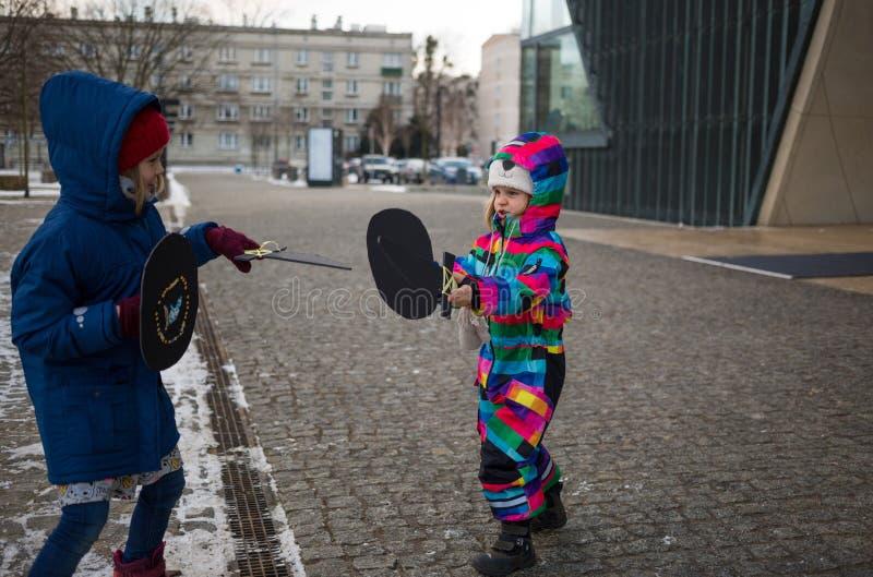 Dzieci bawić się z kartonowymi kordzikami outdoors obraz royalty free