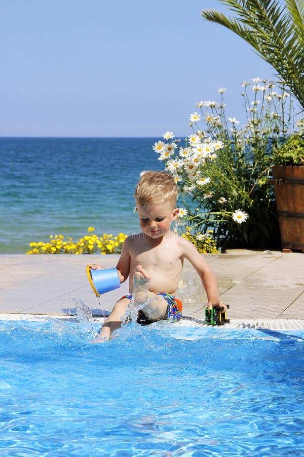 Dzieci bawią się blisko gromadzą Morze i kwiaty przy tłem fotografia royalty free