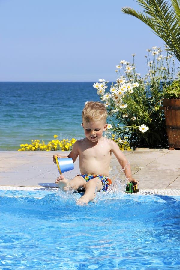 Dzieci bawią się blisko gromadzą Morze i kwiaty przy tłem obrazy royalty free