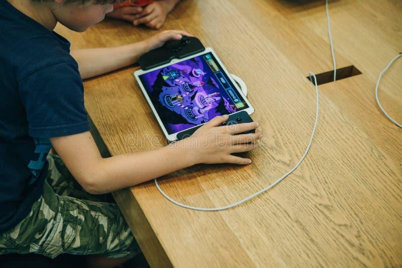 Dzieci bawią się elektroniczna gra na Jabłczanej gemowej konsoli na iPad z specjalnym joystickiem który obraca w a lub obrazy stock