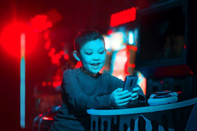 Dzieci bawią się wiszącej ozdoby gry Chłopiec trzyma telefon w jego rękach Neonowy oświetlenie Mobilne gry obrazy royalty free