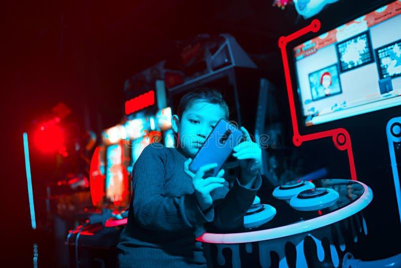 Dzieci bawią się wiszącej ozdoby gry Chłopiec trzyma telefon w jego rękach Neonowy oświetlenie Mobilne gry obraz stock
