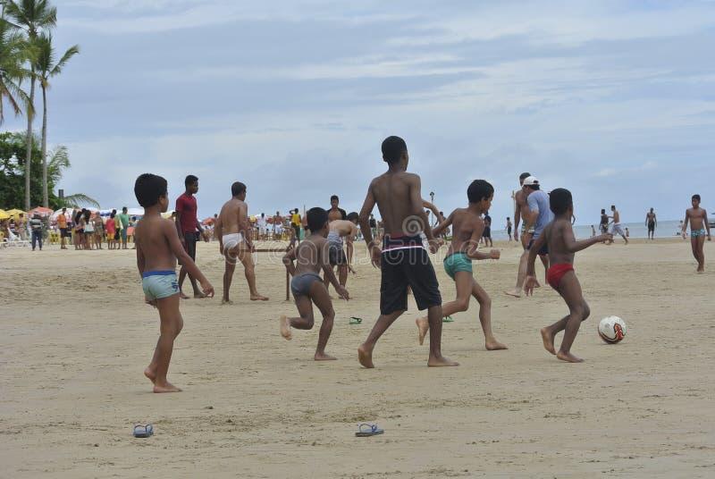 Dzieci bawić się futbol na plaży fotografia royalty free
