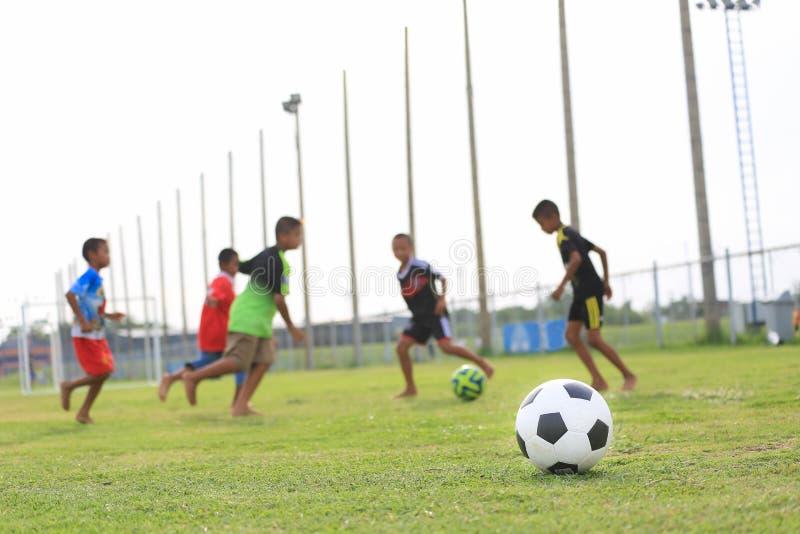 Dzieci bawić się futbol na polu zdjęcia royalty free