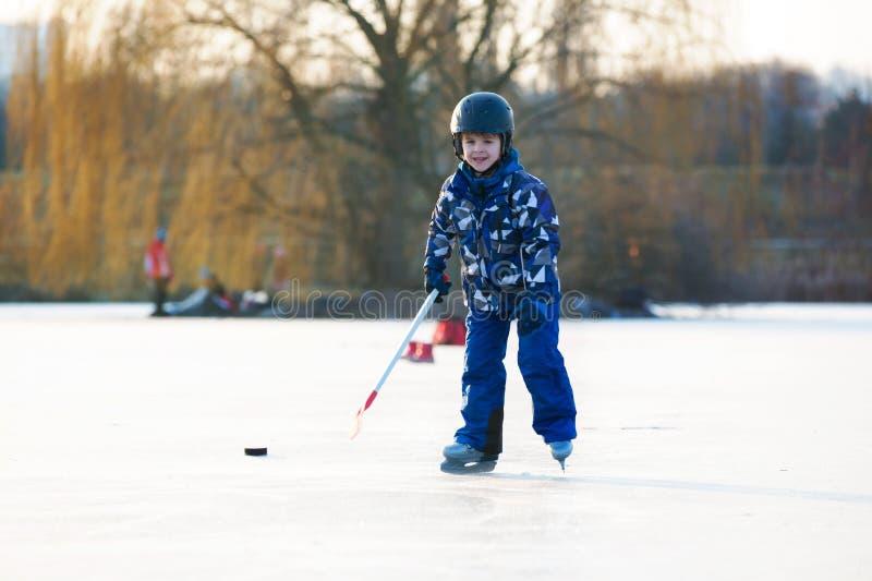 Dzieci, bawić się hokeja i łyżwiarstwo w parku na zamarzniętym jeziorze, zdjęcie stock