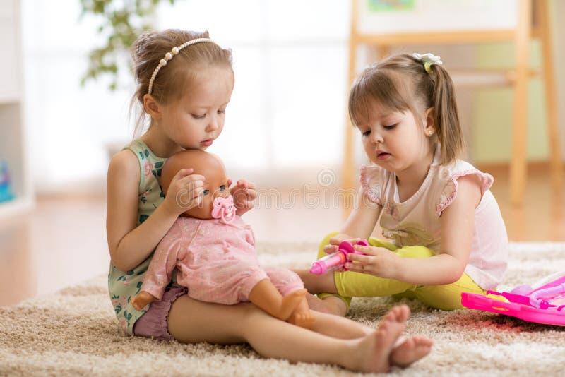 Dzieci bawić się lekarkę z lalą salową zdjęcia stock