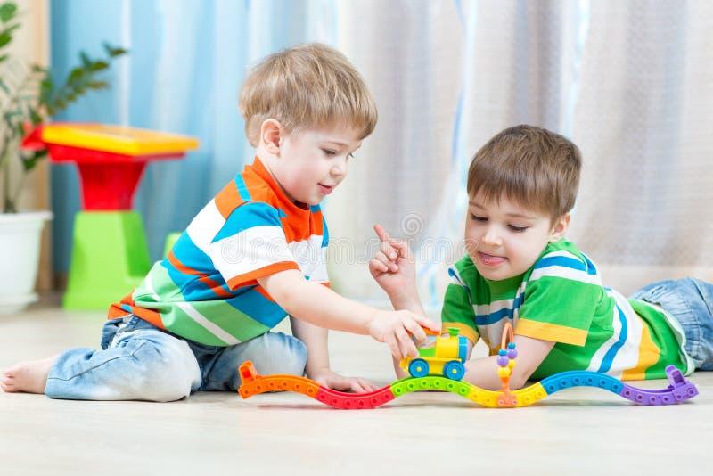 Dzieci bawić się sztachetowej drogi zabawkę w pepinierze fotografia royalty free