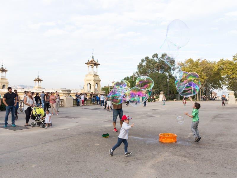 Dzieci bawić się z barwionymi mydlanymi bąblami zdjęcia stock