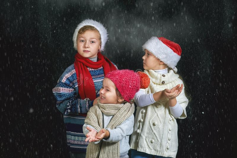 Dzieci bawić się z płatkami śniegu na ciemnym tle obraz royalty free
