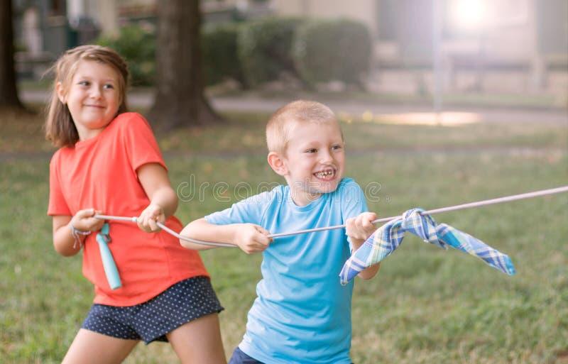 Dzieci bawi? si? za?art? rywalizacj? przy parkiem zdjęcie royalty free