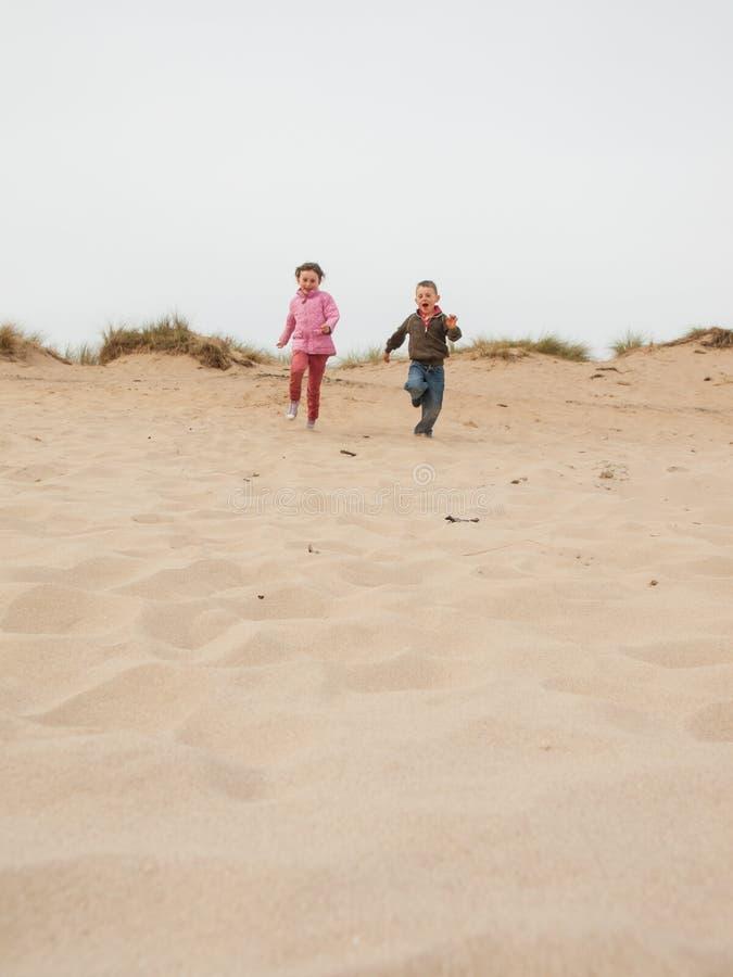 Dzieci biega w dół piasek diunę obraz stock