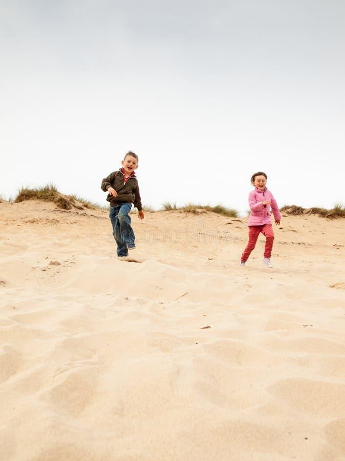 Dzieci biega w dół piasek diunę zdjęcia royalty free
