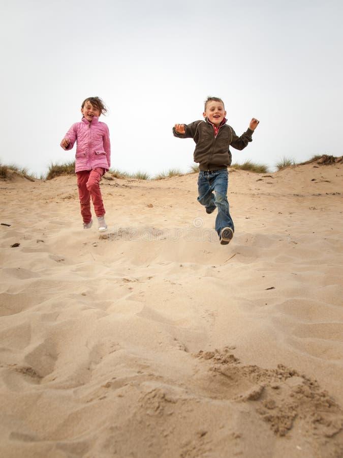 Dzieci biega w dół piasek diunę fotografia stock