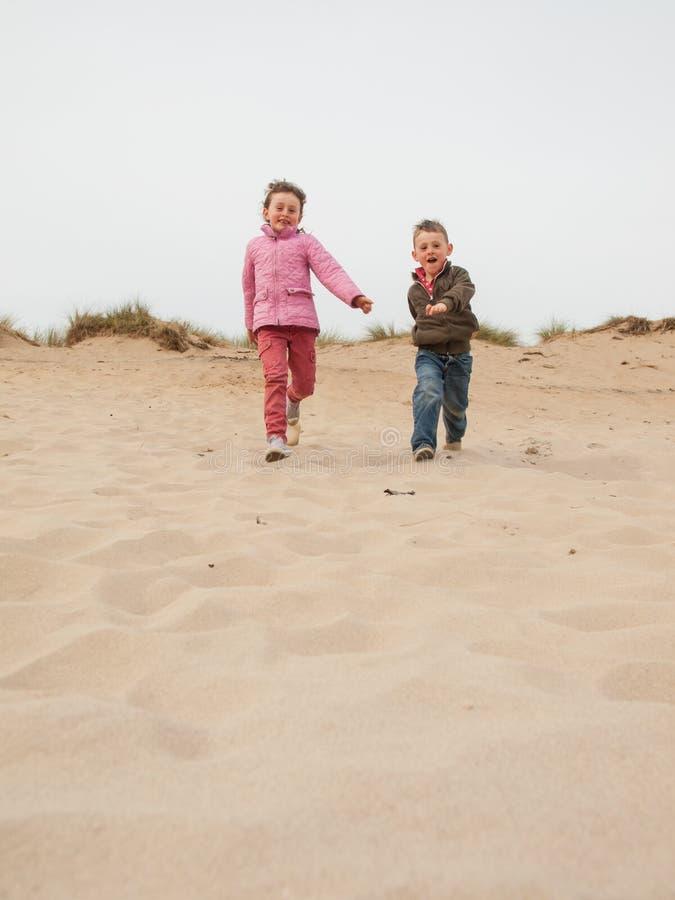 Dzieci biega w dół piasek diunę obrazy stock