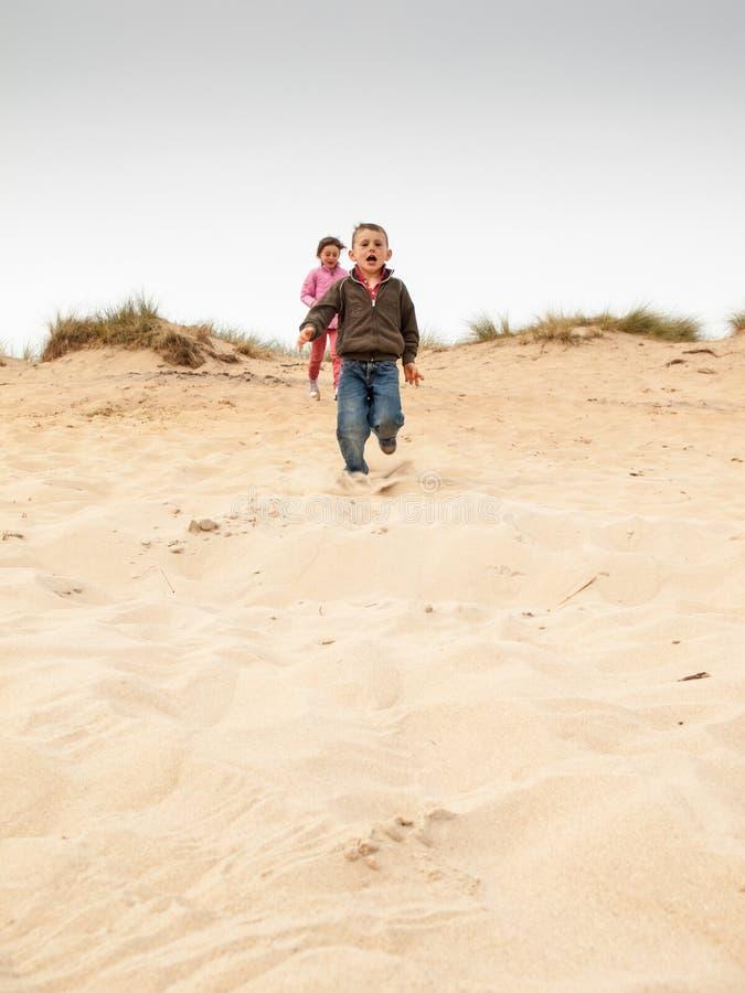 Dzieci biega w dół piasek diunę obraz royalty free