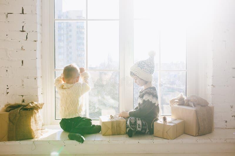 Dzieci brat i siostra preschool wiek siedzą okno na pogodnym święto bożęgo narodzenia i sztuką z prezentów pudełkami zawijającymi zdjęcia royalty free