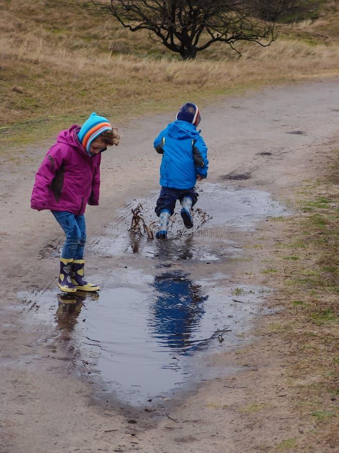 Dzieci bryzga w błotnistej kałuży fotografia stock