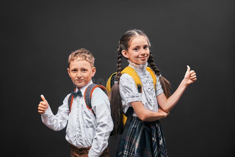 Dzieci chłopiec i dziewczyna ucznie komunikują przy szkołą dziewczyna stojaki z ona z powrotem i oba chłopiec pokazują gest zatwi obraz stock