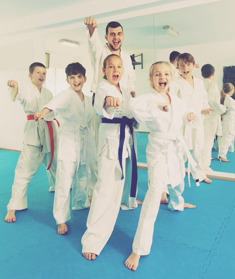Dzieci cieszy się ich szkolenia z trenerem przy karate obrazy royalty free