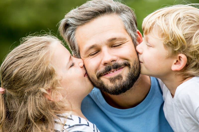 Dzieci dają ojcu buziakowi fotografia royalty free