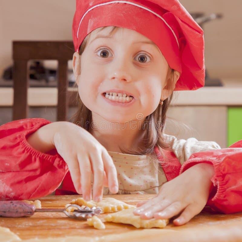 Dzieci gotowa? Mała śmieszna dziecko dziewczyna w szefa kuchni kapeluszu bawić się z ciastem i ma zabawę w kuchni zdjęcie stock