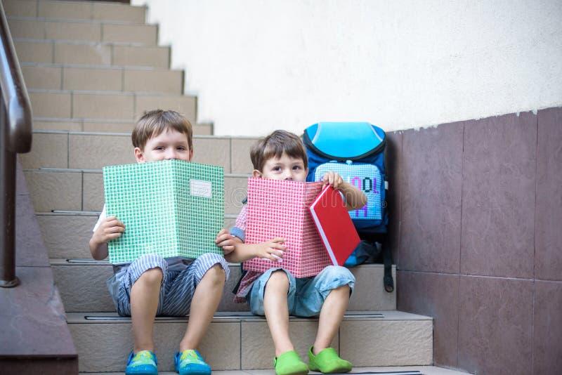 Dzieci iść z powrotem szkoła Początek nowy rok szkolny po wakacje Dwa chłopiec przyjaciela z plecakiem i książkami na pierwszy sc obraz royalty free