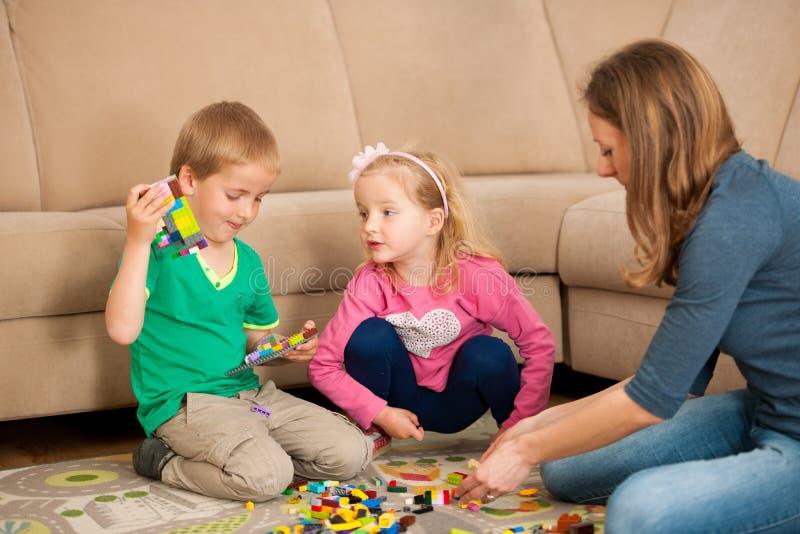 Dzieci i ich matka bawić się z blokami na ziemi zdjęcie royalty free