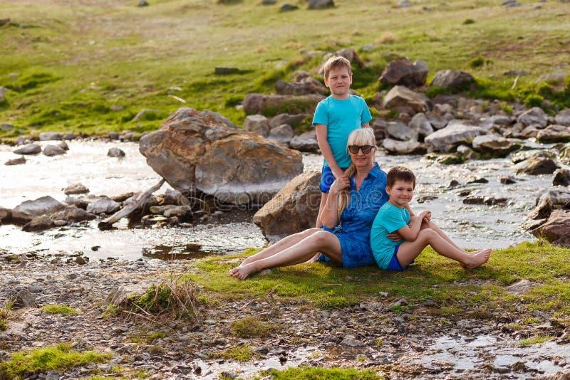 Dzieci i pięćdziesięcioletni kobiety obsiadanie na trawie blisko rzeki obrazy royalty free