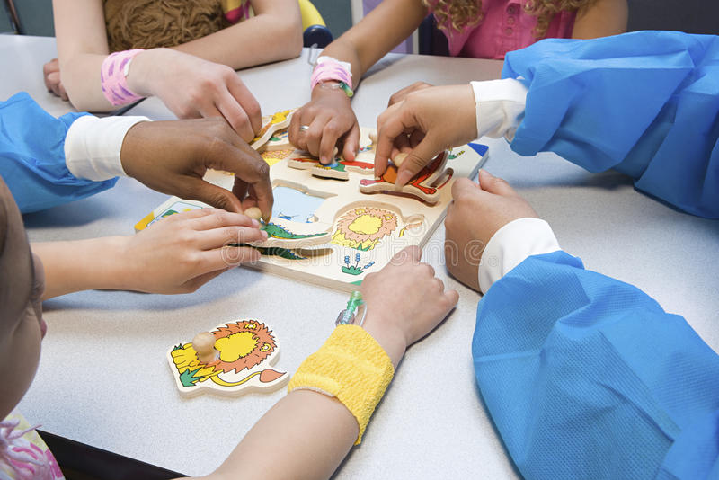Dzieci i pielęgniarki bawić się z łamigłówką obrazy royalty free