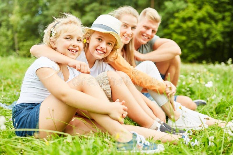 Dzieci i rodzice siedzą zrelaksowanego w trawie obrazy stock