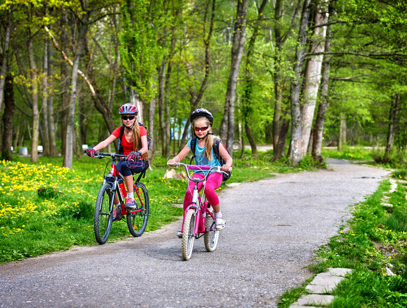 Dzieci jadą bicykl na zielonej trawie i kwiatach w parku obraz stock
