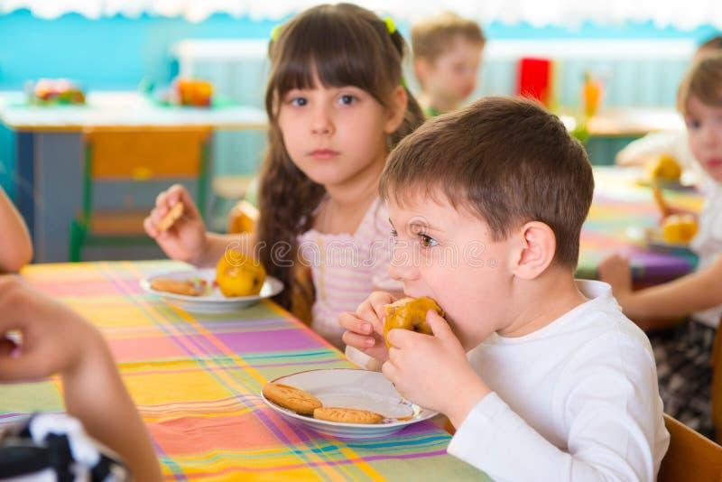 Dzieci je piec ciastka i jabłka przy daycare zdjęcie royalty free