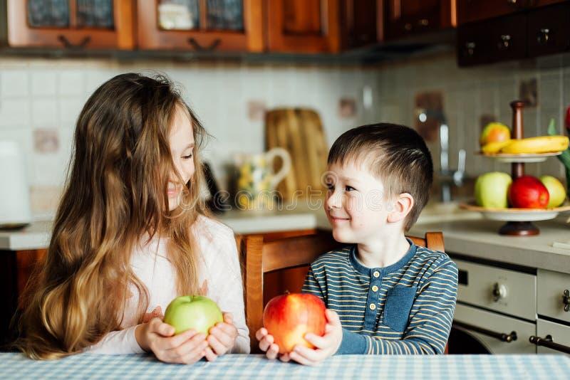 Dzieci jedzą jabłka w kuchni przy rankiem Brat i siostra trzymamy jabłka w ich rękach obraz royalty free