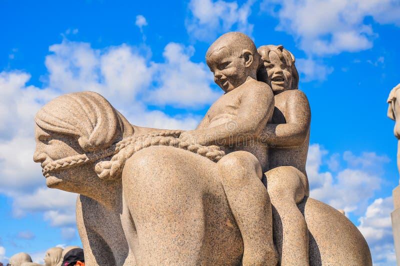 Dzieci jedzie ich macierzystą rzeźbę w Vigeland parku, Oslo zdjęcia stock