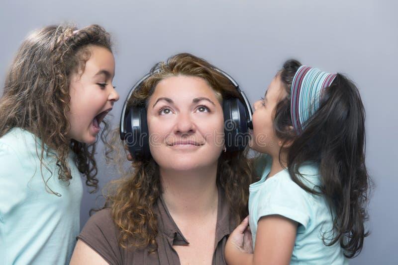 Dzieci krzyczy przy matką podczas gdy ona słucha muzyka obrazy stock