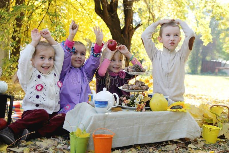 Dzieci ma zabawę na pinkinie pod jesień liśćmi zdjęcia royalty free
