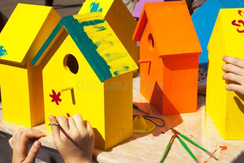Dzieci maluje birdhouses jaskrawych kolory pomarańcze i kolor żółty zdjęcie royalty free