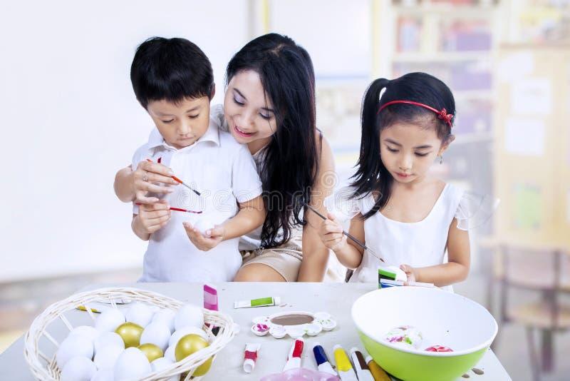 Download Dzieci Maluje Jajka W Klasie Obraz Stock - Obraz złożonej z szczęśliwy, kolory: 28964293
