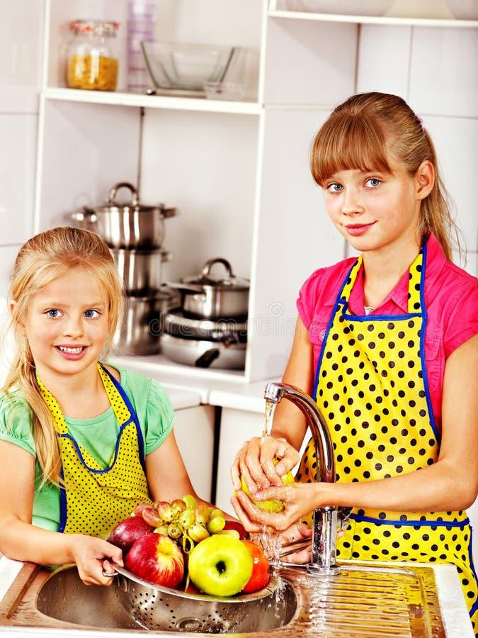 Dzieci myje owoc przy kuchnią. obraz royalty free