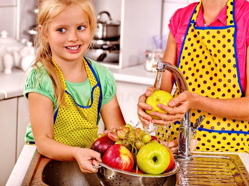 Dzieci myje owoc przy kuchnią zdjęcia stock
