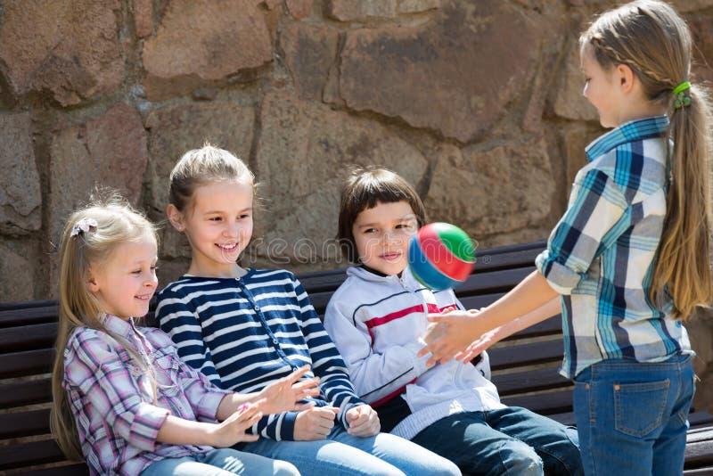 Dzieci na ławce bawić się z piłką obrazy royalty free