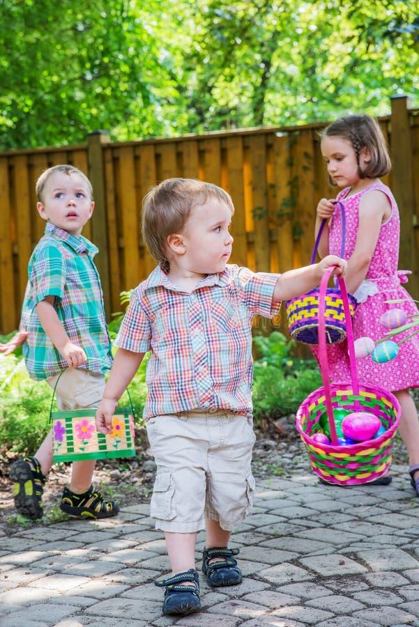 Dzieci na Wielkanocnego jajka polowaniu Outside obraz stock