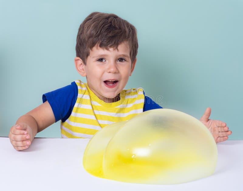 Dzieci nadymają dużego bąbel od różowią szlamowego i żółty śluzowacieje zdjęcia stock