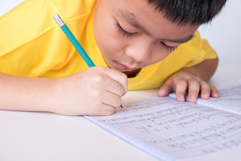 Dzieci odrabiające pracę domową piszące w notesie w domu chłopiec ma 8 lat studiujący w klasie podstawowej w klasie 2 list w zdjęcie royalty free